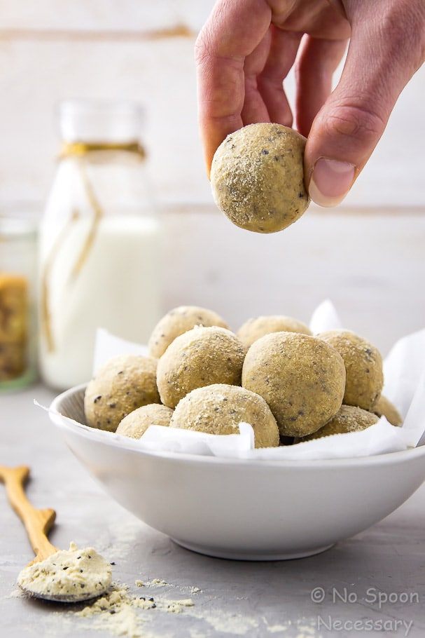 Angled Shot of No Bake Honey Nut Vanilla Protein Energy Bites in a bowl lined with parchment paper and a hand lifting one bite out of the bowl