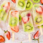 Overhead, landscape shot of Strawberry Kiwi Mojito Boozy Popsicles on a pink plate lined with ice cubes with fresh strawberries and sliced kiwis strewn about the shot.