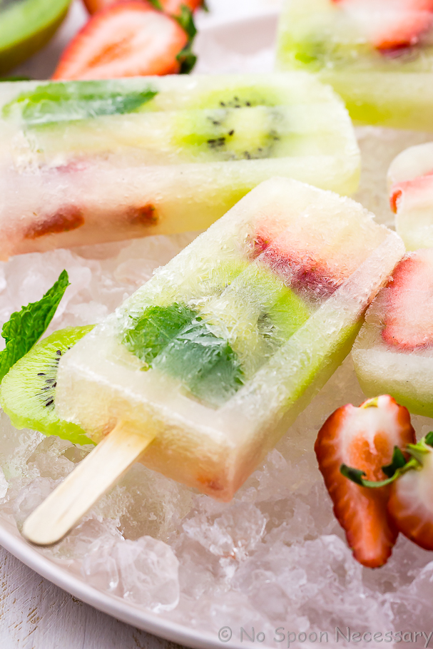 Angled close up shot of a Strawberry Kiwi Mojito Popsicle with other popsicles, strawberries, kiwi and mint blurred in the background and forefront
