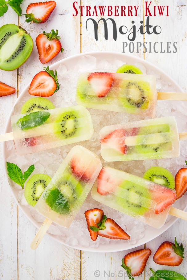 Overhead shot of Strawberry Kiwi Mojito Boozy Popsicles on a pink plate with ice, sliced strawberries, kiwis and fresh mint leaves.