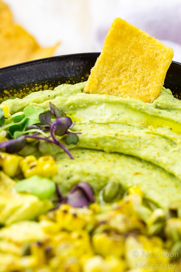 Close up shot of a pita chip dipped into Avocado Sriracha Hummus with grilled corn blurred in the forefront