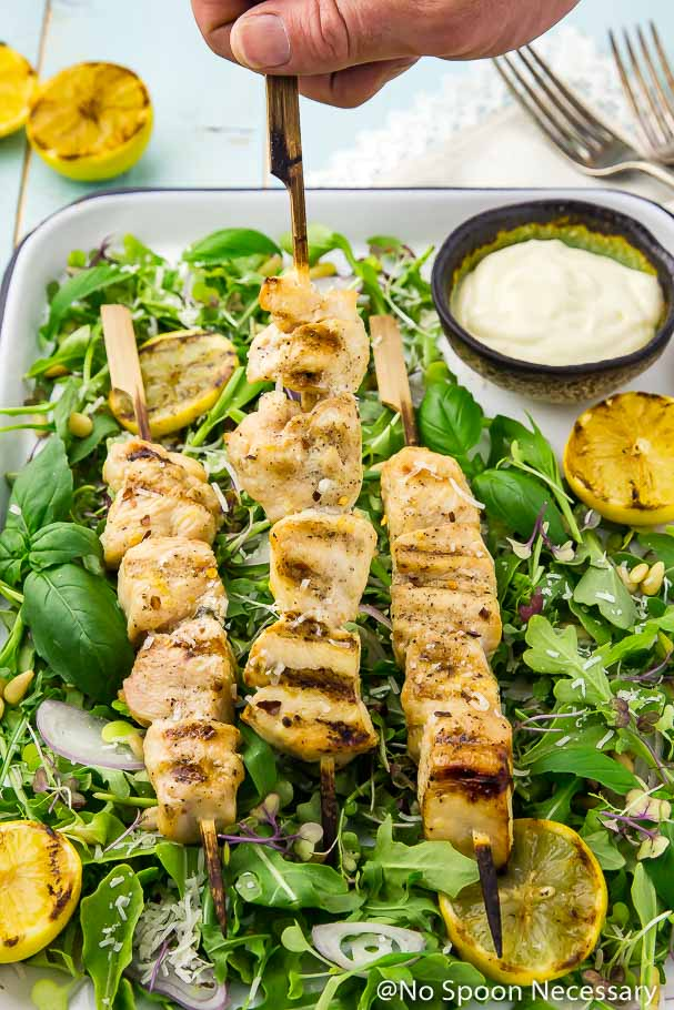 A hand grabbing a chicken skewer from a tray of Grilled Honey Lemon Chicken Skewers on a bed of Arugula and Basil Salad