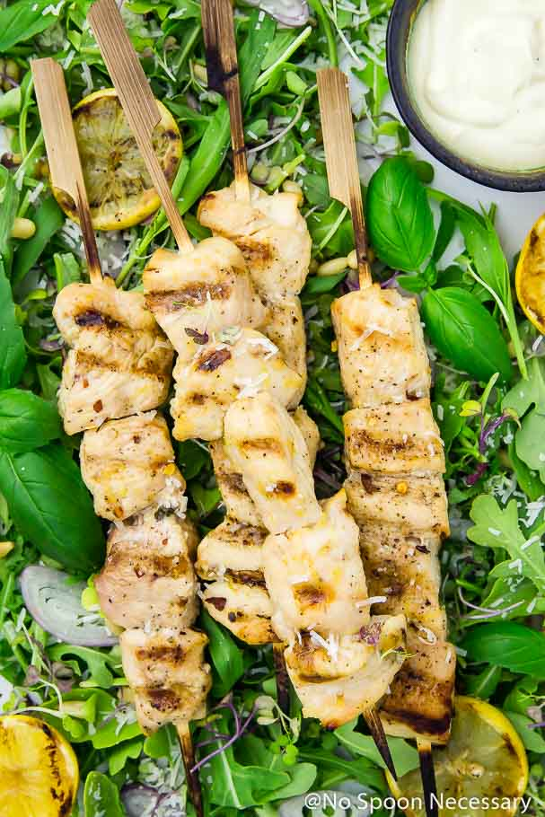 Overhead up-close shot of four overlapping Grilled Honey Lemon Chicken Skewers on a bed of Arugula and Basil Salad, with a bowl of lemon yogurt dip in the right corner