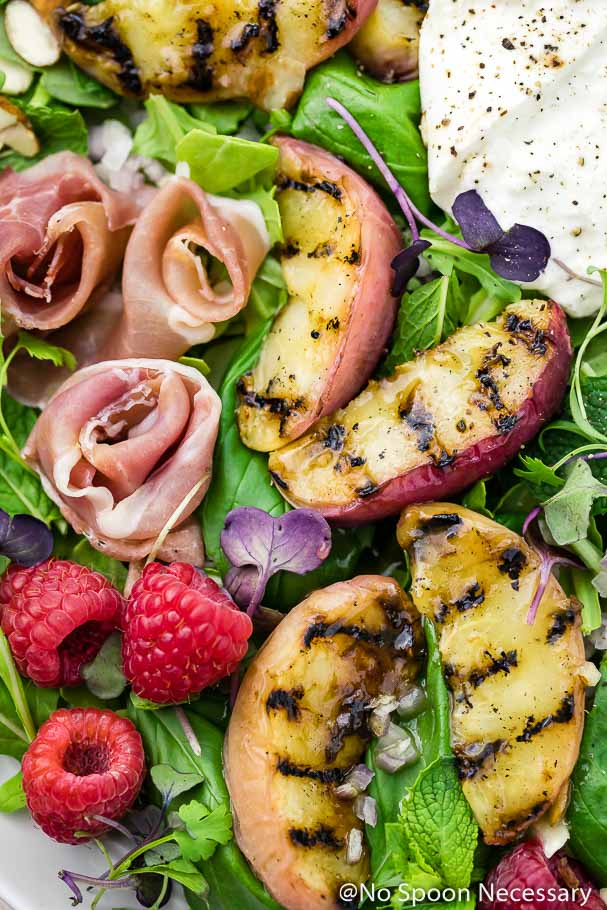 Overhead, up-close shot of Grilled Peach, Burrata, Prosciutto & Raspberry Salad with Honey Balsamic Vinaigrette