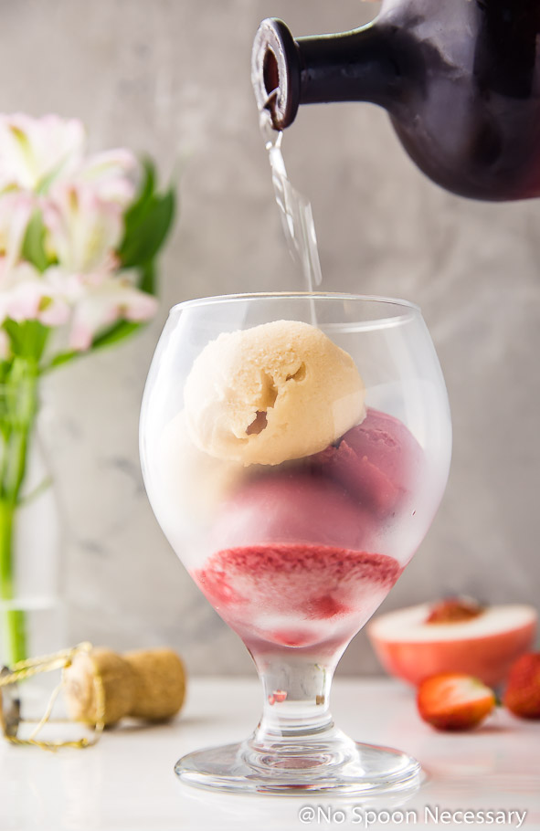 Photo of liqueur being poured into a brandy glass containing scoops of peach and strawberry sorbet; with flowers, a champagne cork and a fresh peach and strawberries in the background. (The second step in the recipe to make a Peach Strawberry Sorbet Rosé Float)