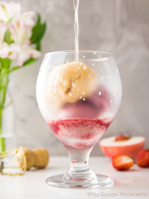 Straight on shot of a stream of Rosé pouring into a glass over scoops of peach and strawberry sorbet with flowers, a champagne cork, a cut peach and strawberries in the background. (An artistic photo of the third step in the recipe to make a Peach Strawberry Sorbet Rosé Float)