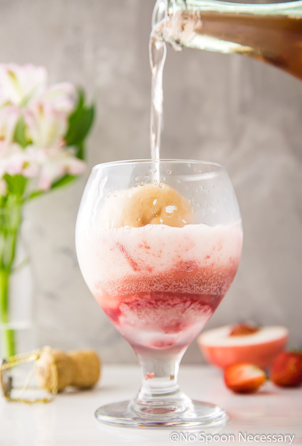 Straight on shot of Rosé being poured over scoops of peach and strawberry sorbet in a brandy glass with flowers, a champagne and fresh strawberries and peach in the background