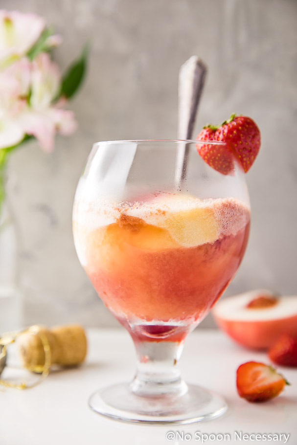 Straight on shot of a glass of Peach Strawberry Sorbet Rosé Float with a strawberry garnish and a spoon in the glass