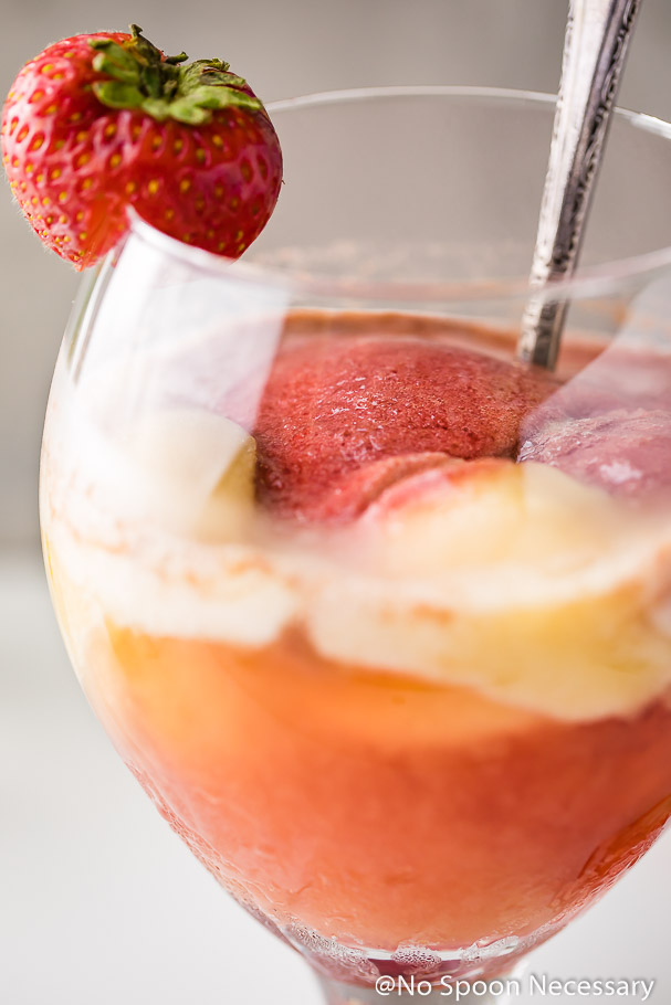 Close up shot of a glass of Peach Strawberry Sorbet Rosé float with a strawberry garnish and a spoon in the glass