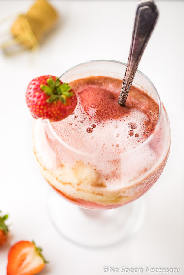 Angled, overhead shot of a glass of Peach Strawberry Sorbet Rosé float with a strawberry garnish and a spoon in the glass; a champagne cork and strawberries in the background