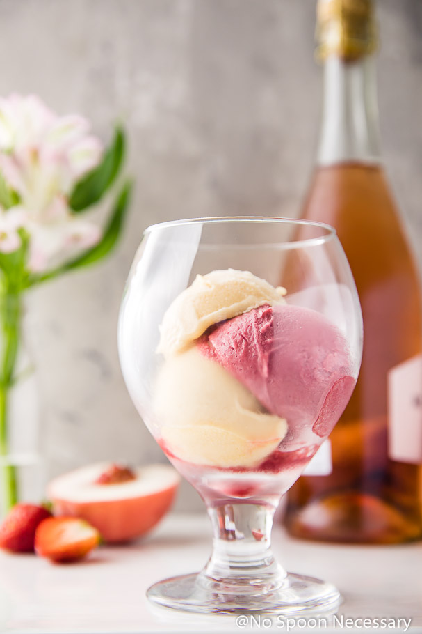 2 scoops of peach sorbet and one scoop of strawberry sorbet in a brandy glass with a bottle of Rosé, pink flowers, a cut peach and strawberries in the background