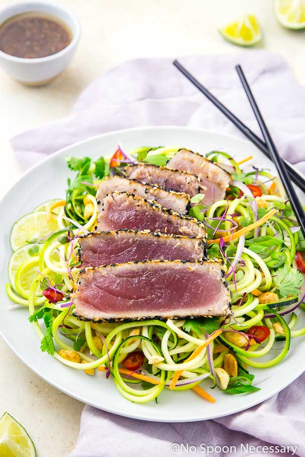 Angled shot of a white plate of Spicy Sesame Crusted Tuna with Thai Zucchini Salad; with a small bowl of Asian Dressing, lime wedges, purple linen and black chopsticks in the background