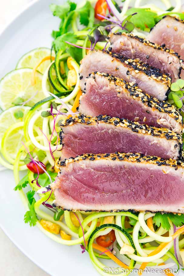 Overhead, up-close shot of rare, pan seared, spicy sesame crusted ahi tuna slices over a bed of Thai zucchini noodles with lime slices in the background