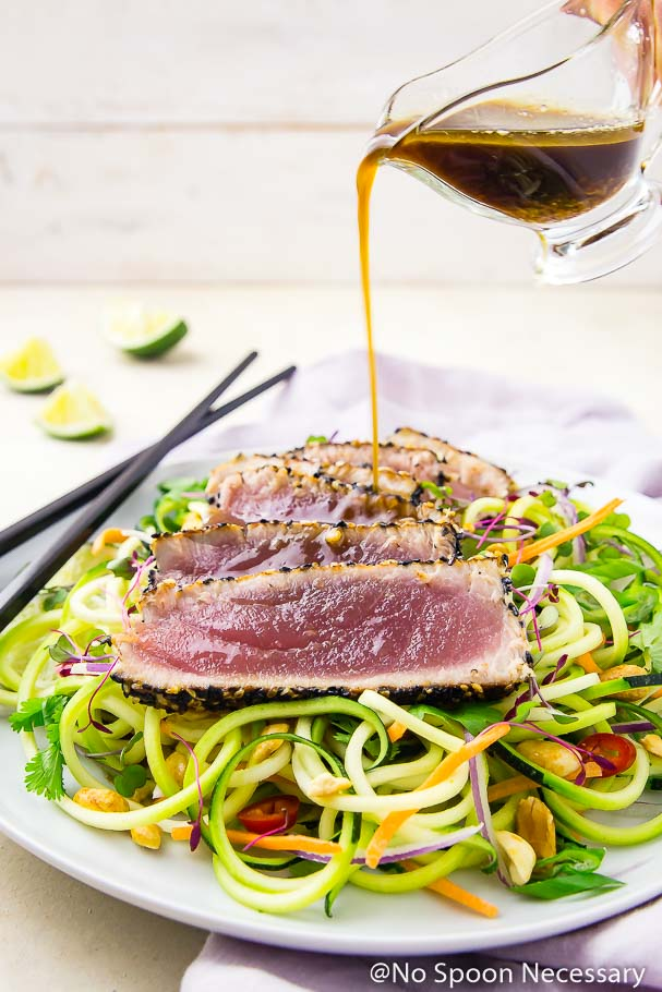 Angled shot of Asian dressing being poured over rare, pan seared, spicy sesame crusted tuna slices on a bed of Thai zucchini noodles with black chopsticks and lime wedges in the background