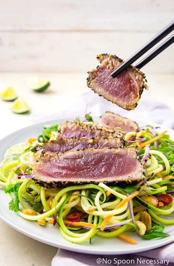 Angled shot of black chopsticks picking up a slice of rare, pan seared, spicy sesame crusted tuna off a white plate of Thai zucchini noodles topped with a sliced filet of sesame crusted tuna