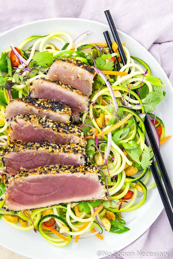 Overhead shot of rare, pan seared, spicy sesame crusted ahi tuna slices on a bed of zucchini noodles with black chopsticks intertwined in the vegetable noodles