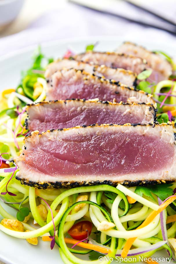 Angled, up-close shot of rare, spicy sesame crusted, pan seared tuna slices over a bed of Thai zucchini noodles