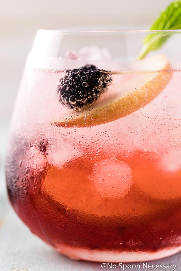 Extreme close up shot of Blackberry Peach Elderflower Cocktail in a short clear glass with a mint sprig garnish