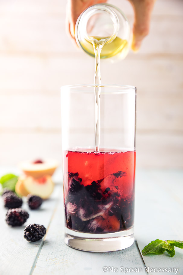 Elderflower liqueur being poured into a tall glass filled with the ingredients for a Blackberry Peach Cocktail; with fresh fruit blurred in the background