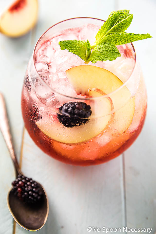 Overhead angled shot of a Blackberry Peach Elderflower Cocktail in a short clear glass with a mint sprig garnish; with a slice of peach and a blackberry on a spoon blurred next to the glass