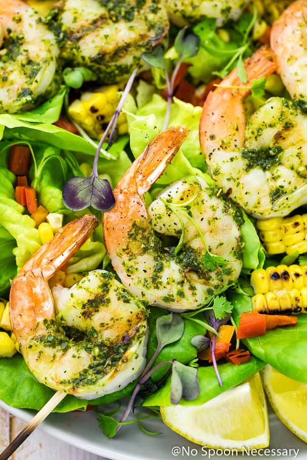 Overhead, up-close shot of Chimichurri Grilled Shrimp & Corn Salad with corn, peppers and lemon wedges with the focus of the shot on the shrimp skewers.
