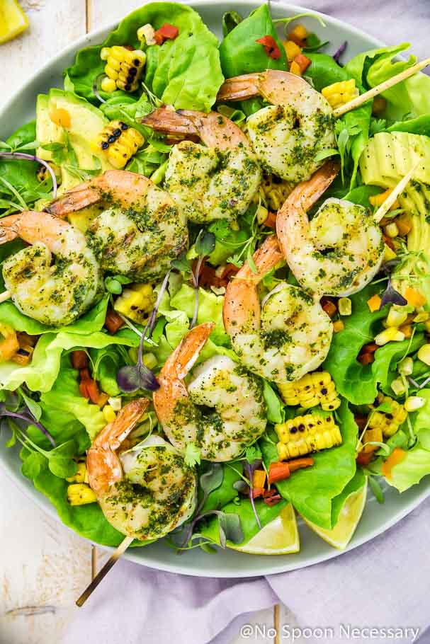 Overhead shot of Chimichurri Grilled Shrimp & Corn Salad with summer peppers and avocado with lemon wedges and a purple linen around the plate.