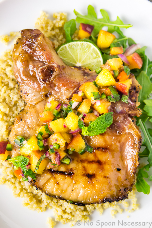 Overhead shot of Ginger Honey Glazed Pork Chops with Peach-Poblano Salsa on quinoa and arugula with a lime wedge.
