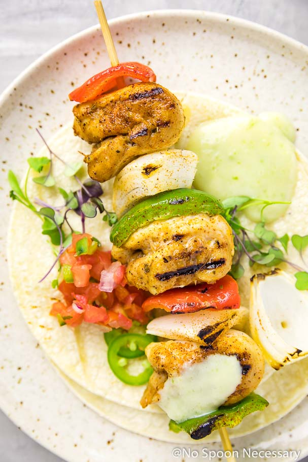 Overhead, up-close shot of a Margarita Fajita Chicken Kebab on a speckled plate with tortillas, micro-greens, pico de gallo, and a dollop of pineapple aioli