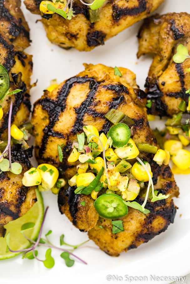 Overhead, up-close shot of a Southwest Buttermilk Grilled Chicken Thigh topped with Corn Salsa, sliced jalapenos and microgreens