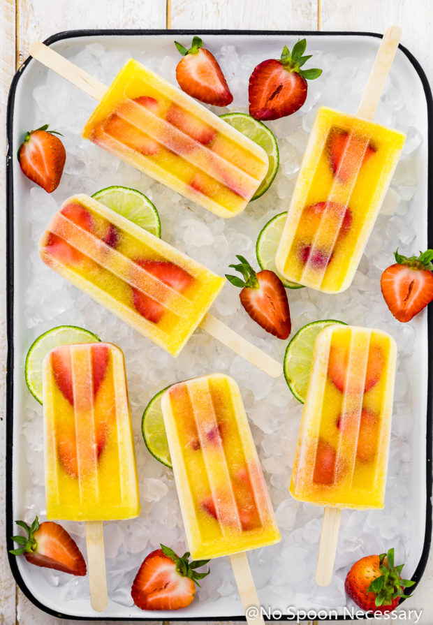 Overhead shot of Strawberry Mango Gin and Tonic Boozy Popsicles on a white tray filled with ice with lime slices and strawberries strewn around the popsicles.