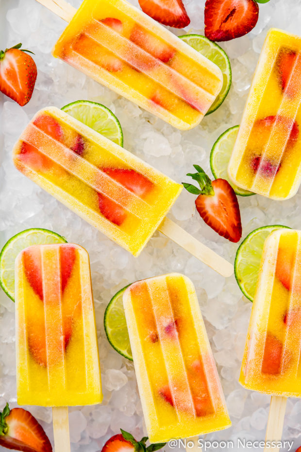 Overhead shot of Strawberry Mango Gin and Tonic Boozy Popsicles on a surface of crushed ice with lime slices and strawberries strewn around the popsicles.