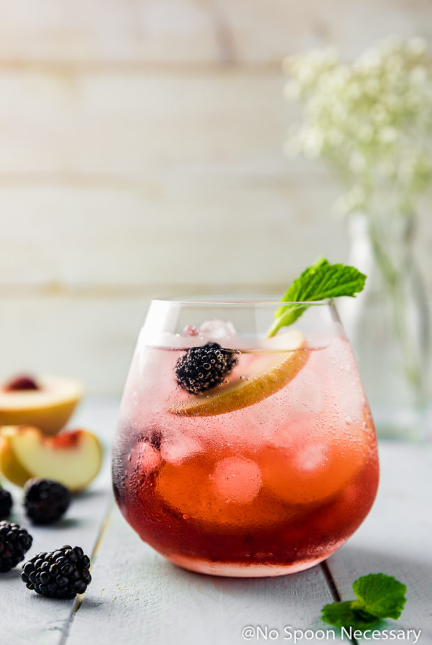 Straight on shot of a Blackberry Peach Elderflower Cocktail garnished with fresh blackberries, peach slices and mint with more fresh fruit surrounding the cocktail glass and a small vase of flowers blurred in the background.