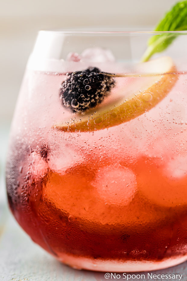 Extreme close up shot of Blackberry Peach Elderflower Cocktail in a short clear glass with a mint sprig garnish.
