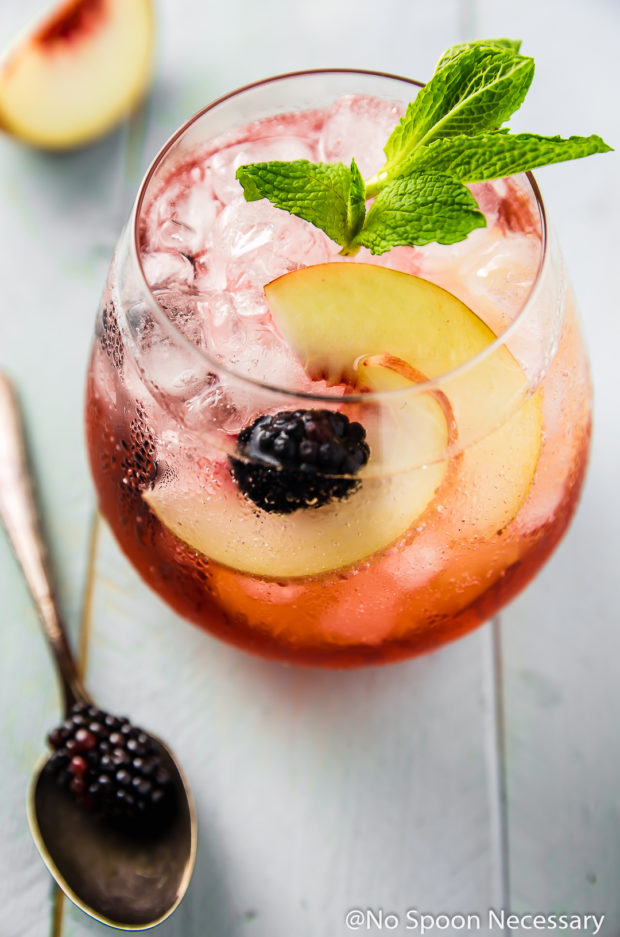 Overhead angled shot of a Blackberry Peach Elderflower Cocktail in a short clear glass with a mint sprig garnish; with a slice of peach and a blackberry on a spoon blurred next to the glass.