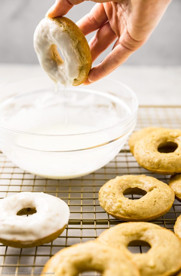 Angled shot of a hand dipping a donuts into a bowl of glaze with other donuts surrounding the bowl of glaze - photo of step 9 of the baked apple cider donut recipe.