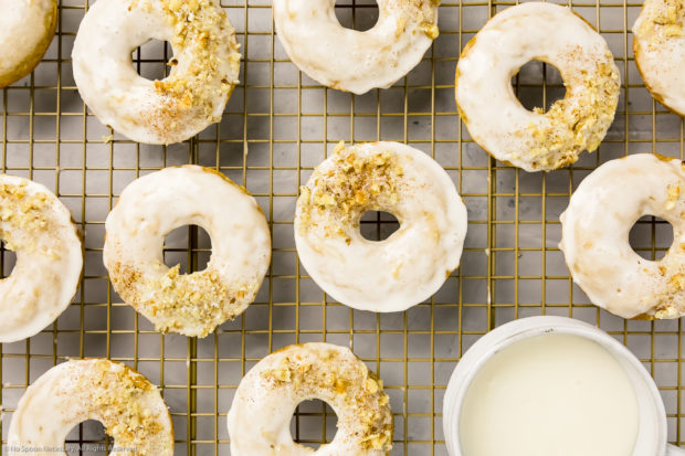 Overhead shot of Baked Apple Cider Donuts on a a gold wire rack with a ramekin of glaze tucked into the corner of the shot.