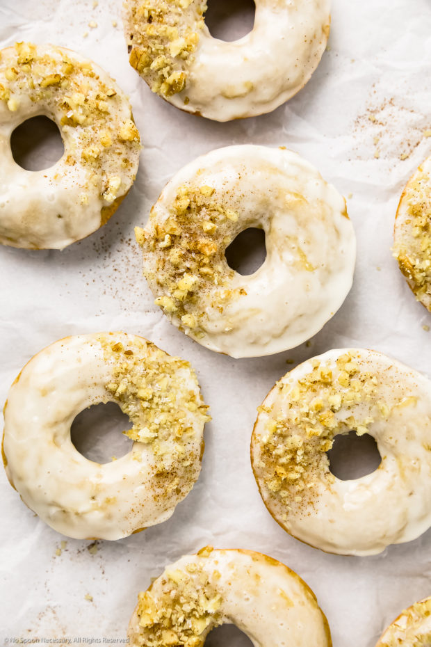 Overhead shot of several baked apple cider donuts topped with crushed walnuts and sprinkles on a wrinkled piece of parchment paper.