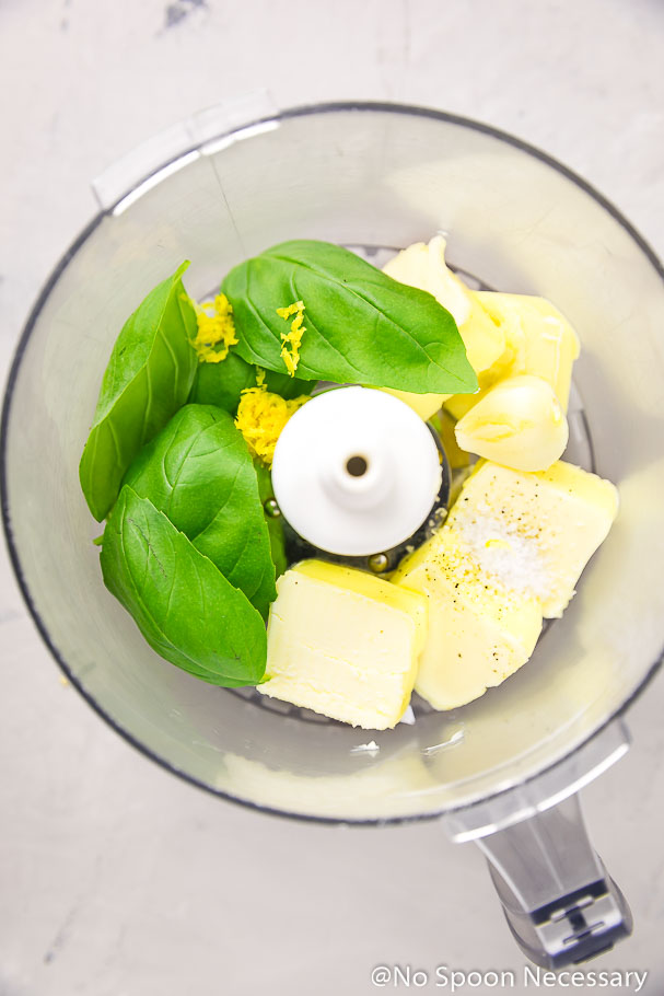 Overhead shot of the ingredients to make Basil Butter in the bowl of a food processor