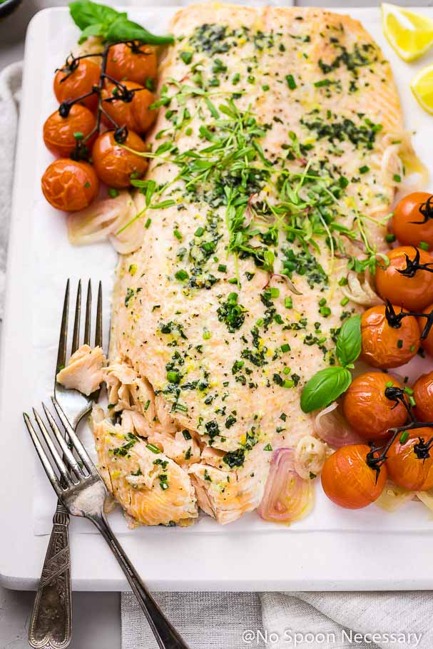 Angled shot of partially flaked and cut into basil butter roasted salmon on a white board with burst tomatoes and two forks