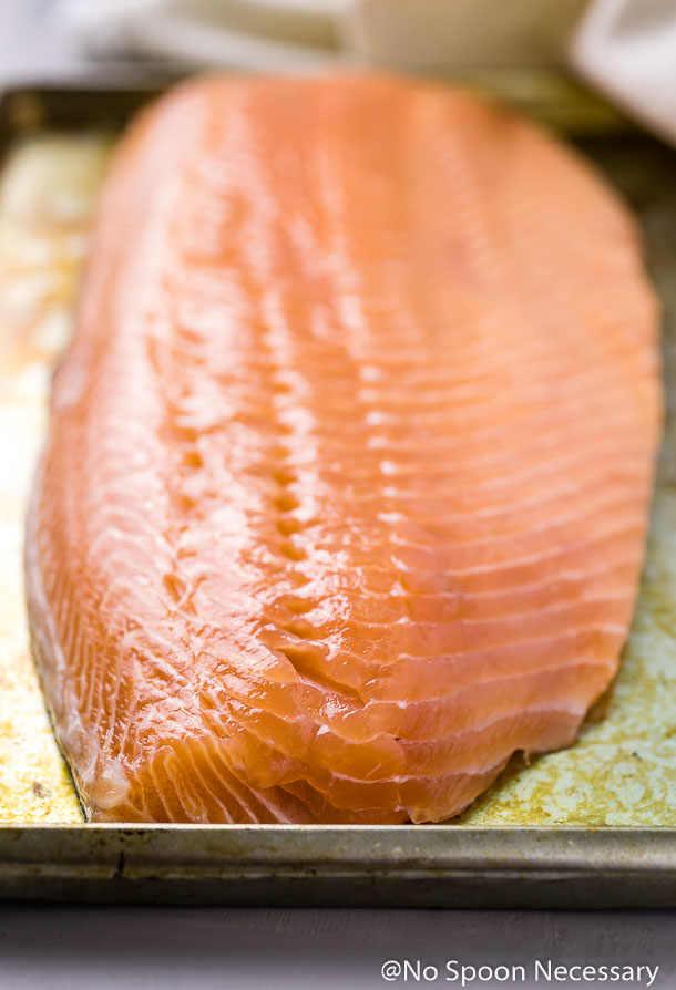 Angled shot of a raw side of salmon on a small antique sheet pan
