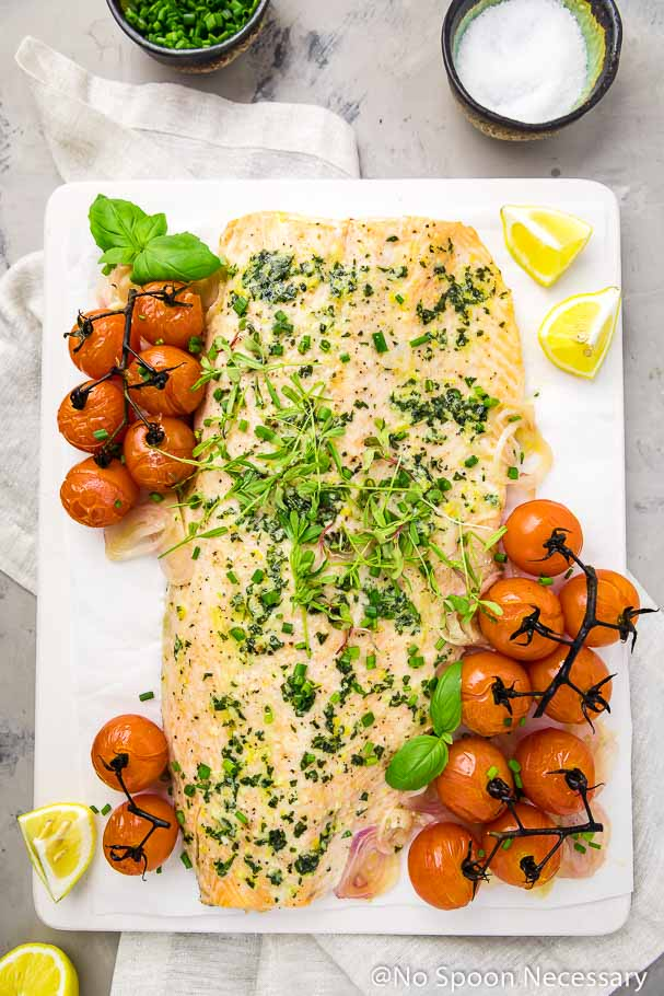 Overhead shot of Basil Butter Roasted Salmon and Burst Tomatoes on a white board with a neutral linen, lemon wedges and bowls of chives and sea salt surrounding the board