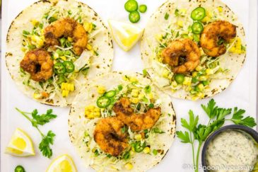Overhead, landscape shot of three Cajun Shrimp Tacos with Spicy Corn Slaw & Remoulade on a white board with lemon wedges, slices of jalapeños, fresh parsley and a small ramekin of remoulade.