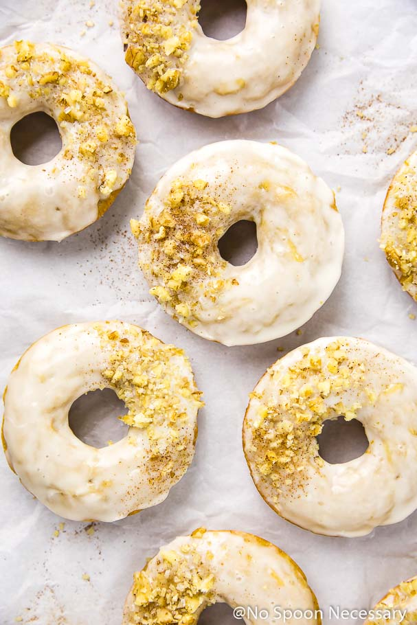 Overhead shot of several glazed cinnamon apple cider baked donuts topped with crushed walnuts and sprinkles on a wrinkled piece of parchment paper.