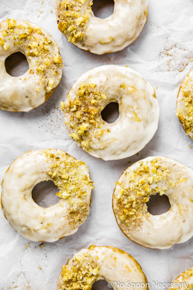 Overhead shot of several baked glazed cinnamon apple cider donuts topped with crushed walnuts and sprinkles on a wrinkled piece of parchment paper.