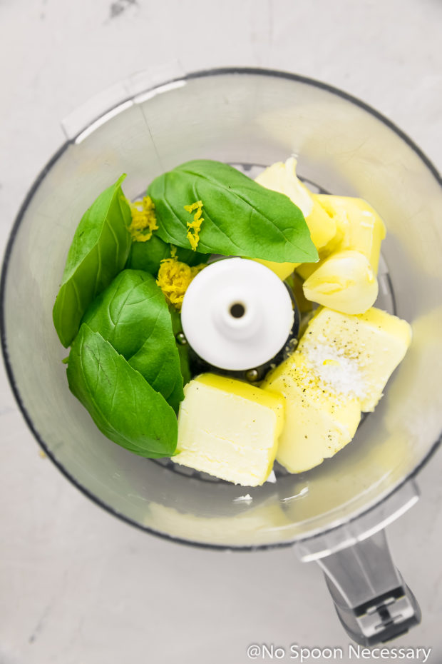Overhead shot of the ingredients to make Basil Butter in the bowl of a food processor.