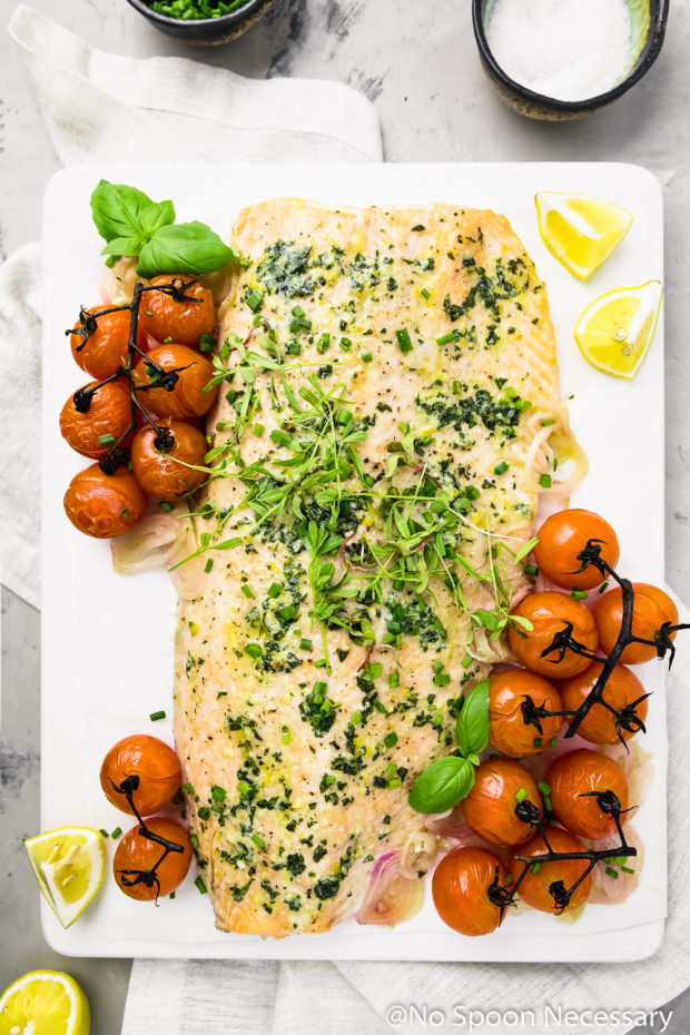 Overhead shot of Oven Baked Basil Butter Salmon with Burst Tomatoes on a white board with a neutral linen, lemon wedges and bowls of chives and sea salt surrounding the board.