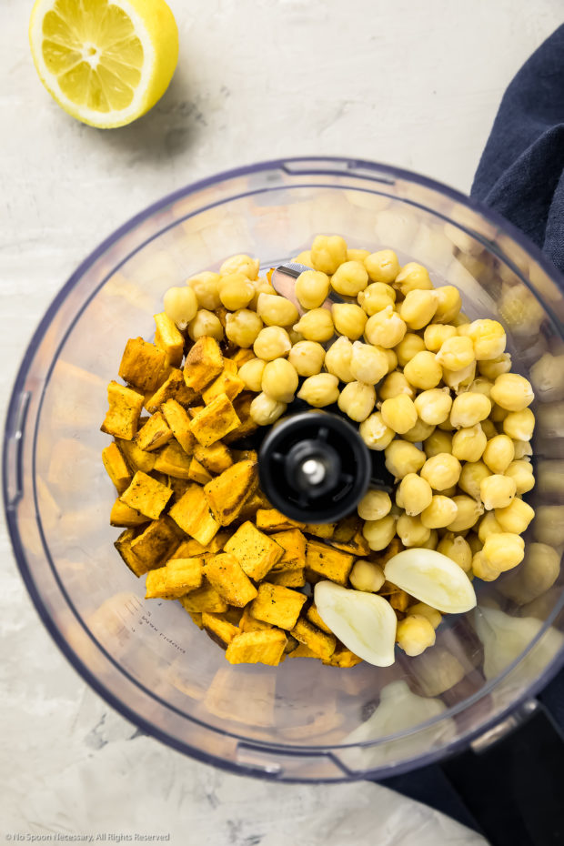 Overhead photo of the ingredients needed to make Sweet Potato Hummus in the bowl of a food processor with a half of lemon and blue linen next to the bowl.