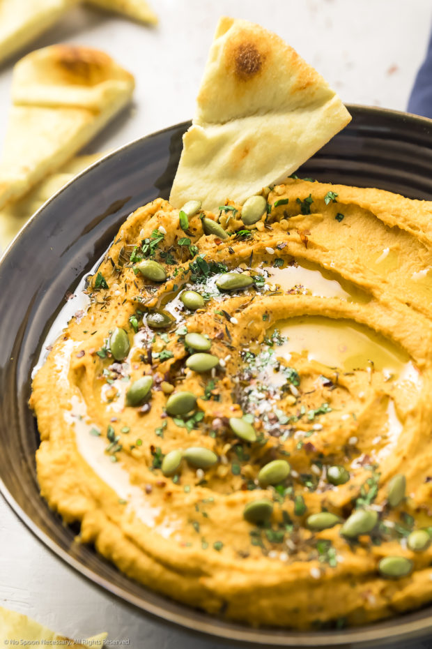 Angled, up close photo of Sweet Potato Hummus in a large brown serving bowl with a pita wedge dipped into the hummus and more pita bread blurred in the background.
