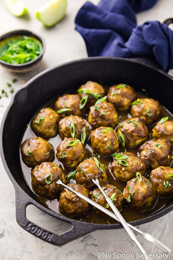 Angled shot of Baked Spiced Hard Apple Cider Glazed Meatballs in a cast iron skillet with two large silver skewers inserted into two meatballs; blue linen, small bowl of sliced green onions and 2 apple wedges blurred in the background