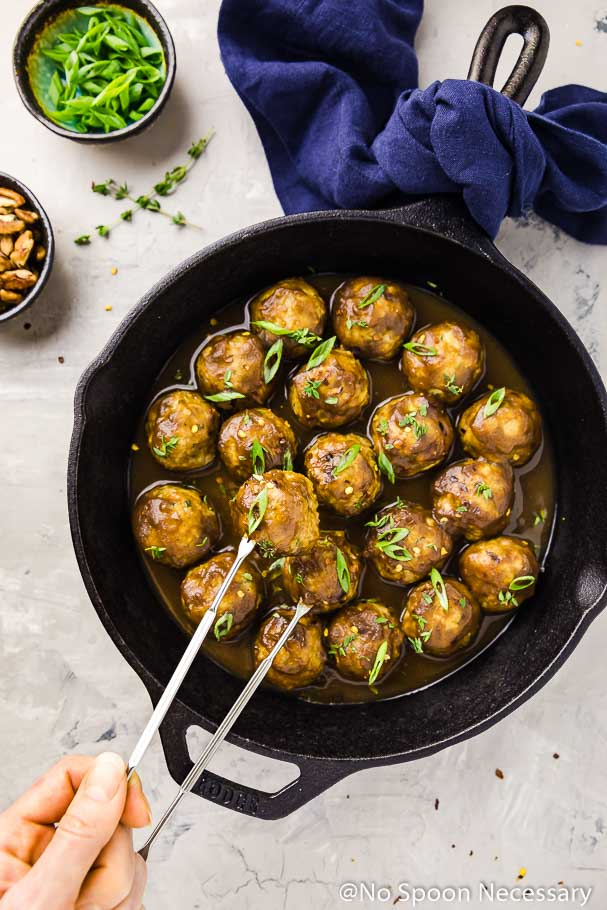 Overhead shot of Baked Spiced Hard Apple Cider Glazed Meatballs in a cast iron skillet with hand holding a silver skewer piercing one meatball and picking it up.
